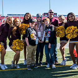Winner of the Mitsubishi Las Vegas Bowl sweepstakes with his family standing with cheerleaders and a mascot.