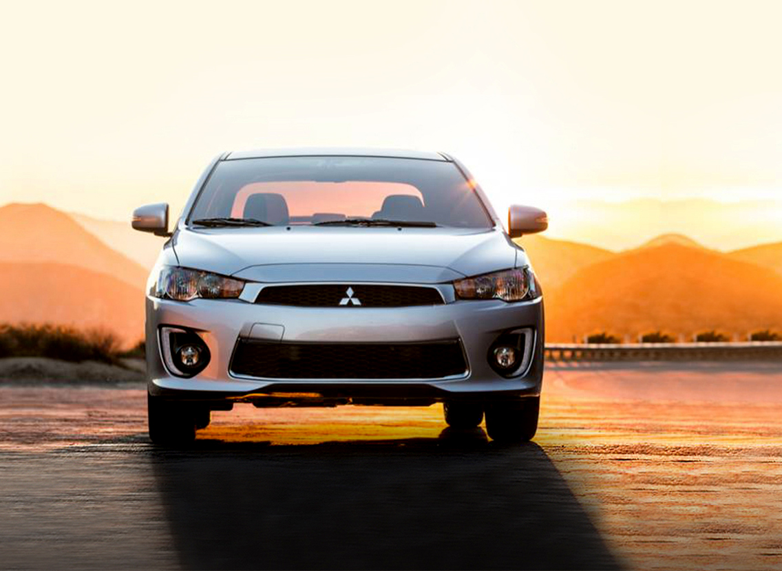Mitsubishi Lancer parked on the road during a sunset