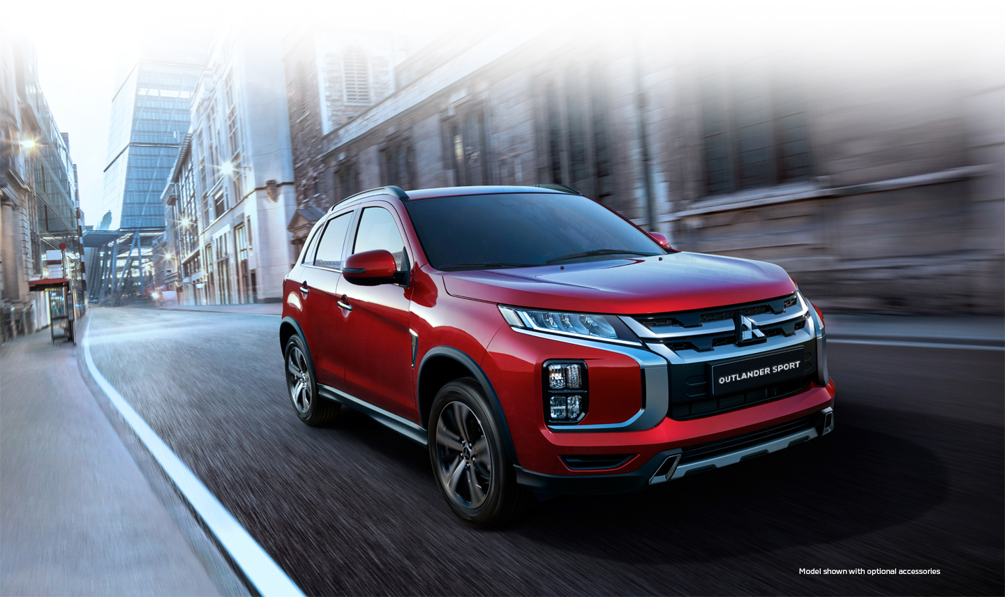 A red 2020 Mitsubishi Outlander sport driving down a city street
