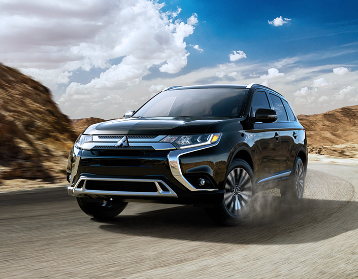 Black 2019 Mitsubishi Outlander driving on paved road