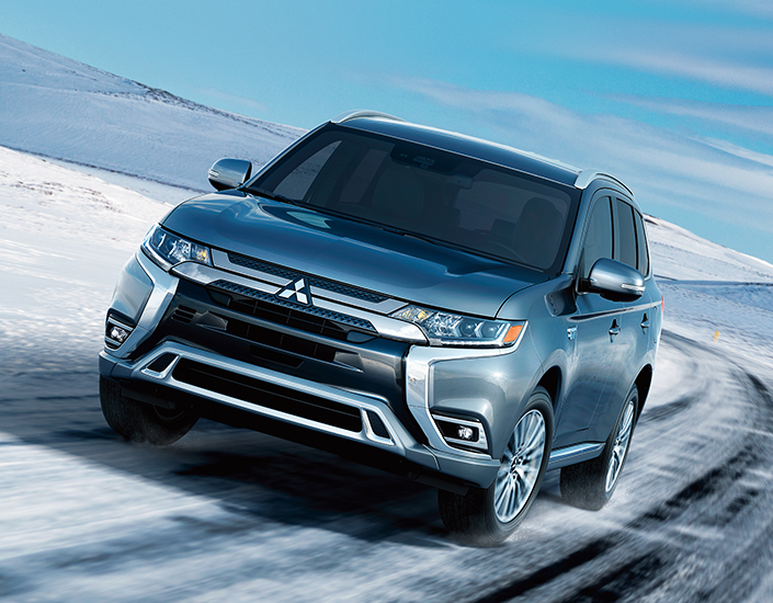 Front view of a silver Mitsubishi Outlander driving on a snowy road