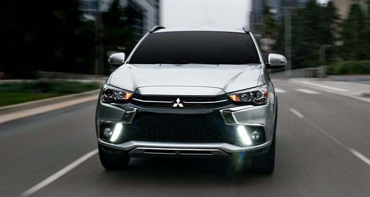 Front view of an Mitsubishi Eclipse Cross in silver driving in a city