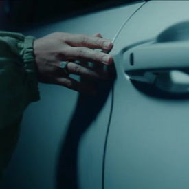A play button superimposed over a woman taking a picture outside the window of a 2022 Mitsubishi Outlander.