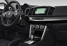 Lancer's interior shown with high-contrast meters, gloss black accents and an available Navigation system.