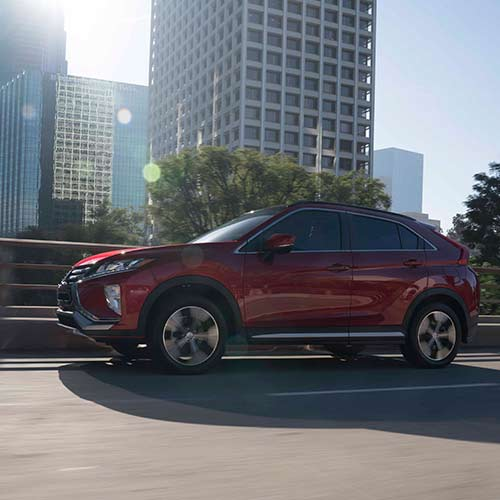 A red 2020 Mitsubishi Eclipse Cross crossover driving on the bridge
