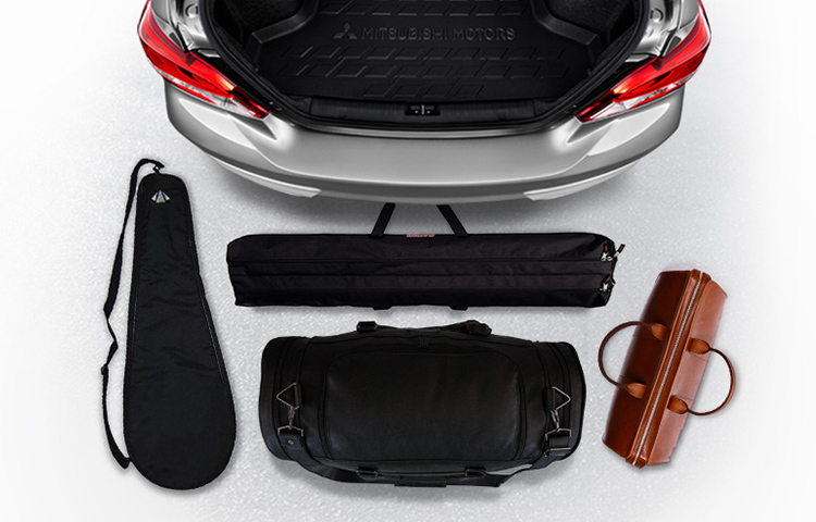 The open trunk of a silver 2019 Mitsubishi Mirage G4 with various items around it to demonstrate its cargo space.