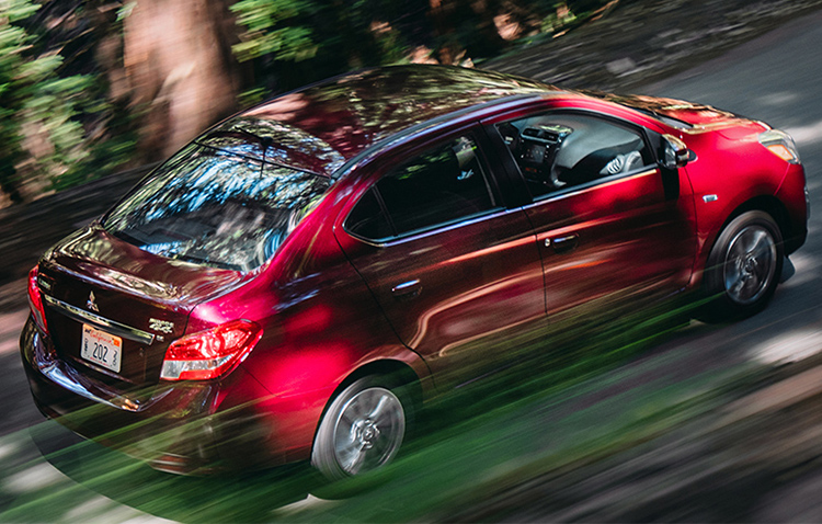 An overhead shot of a 2019 Mitsubishi Mirage G4 cruising down a road in the woods.