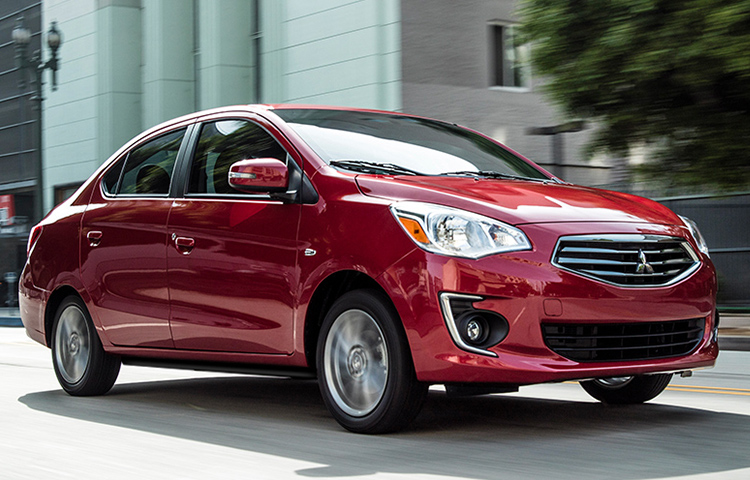 A metallic red 2019 Mitsubishi Mirage G4 driving down the streets.