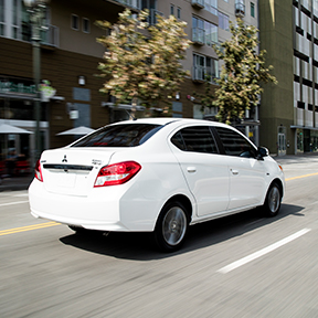 Rearview of a 2019 Mitsubishi Mirage G4 in White driving in the city.
