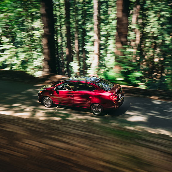 A red 2020 Mitsubishi Mirage G4 driving in the woods