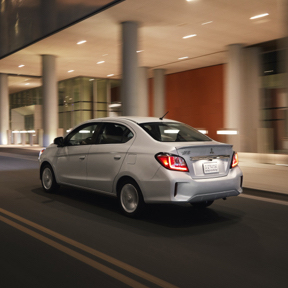 The back of a silver 2021 Mitsubishi Mirage G4 parked outside a stylish modern building with columns.