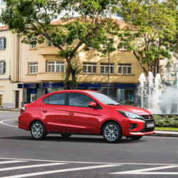 A red 2021 Mitsubishi Mirage G4 parked besides a fountain.