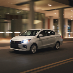 The front of a silver 2021 Mitsubishi Mirage G4 driving down a city street at night.