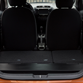 Rearview of the 2019 Mitsubishi Mirage with the hatch open and seats folded down to display cargo space.