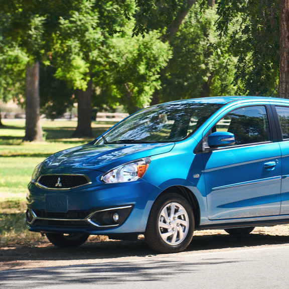 A blue 2020 Mitsubishi Mirage parked next to a beautiful forest.