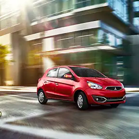 A side view of a red 2020 Mitsubishi Mirage driving down a city street.