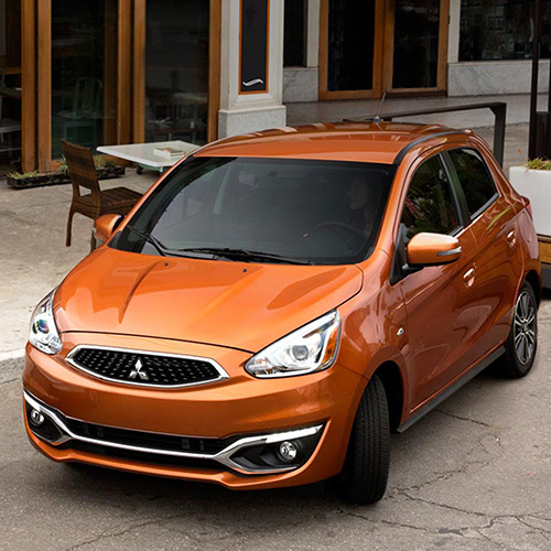 Front view of an orange 2020 Mitsubishi Mirage compact car parking outside a store.