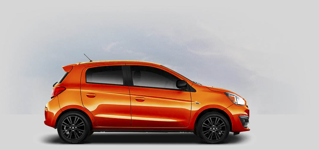 A 2020 Mitsubishi Mirage LE with sunrise orange metallic color.
