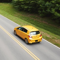 An aerial view of a yellow 2021 Mitsubishi Mirage driving down a forested highway.