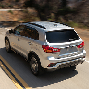 Rearview of a silver 2019 Mitsubishi Outlander Sport SUV driving on a road.