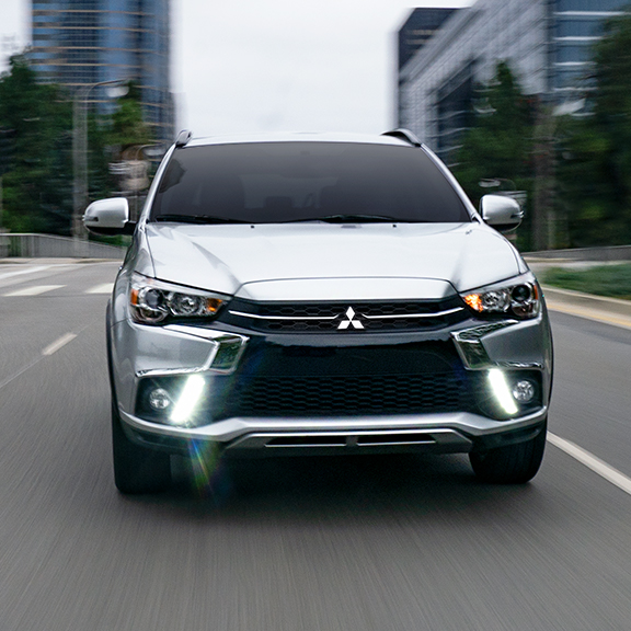 Front view of a silver 2019 Mitsubishi Outlander Sport SUV driving on a paved road in the city.