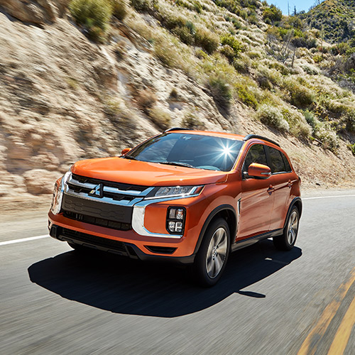 A orange 2020 Mitsubishi Outlander Sport driving down the road in the country