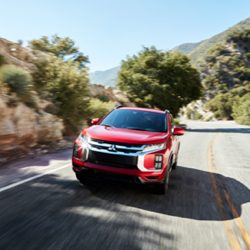 A red 2021 Mitsubishi Outlander Sport driving down a beautiful country road.