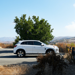 A white 2021 Mitsubishi Outlander Sport parked along a country road.
