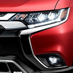 Close up of the exterior LED headlights on a red 2020 Mitsubishi Outlander SUV.