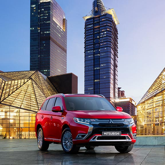 A red 2020 Mitsubishi Outlander PHEV parked in the city