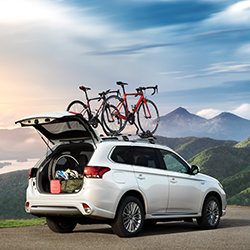 Exterior rear side view of the 2020 Mitsubishi Outlander PHEV with its rear gate open and bikes attached to the roof, parked in the mountains.