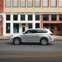 Side profile of a silver 2021 Mitsubishi Outlander PHEV driving in a city road