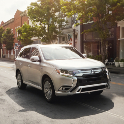 Front and side profile of a pearl white 2021 Mitsubishi Outlander PHEV driving on the road