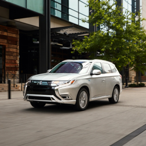Front and side profile of a 2021 Mitsubishi Outlander PHEV driving on the road